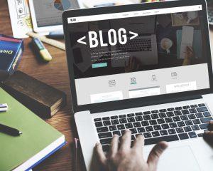 Osoba prowadzi bloga, pisze na laptopie. Na ekranie widoczny jest blog firmowy.