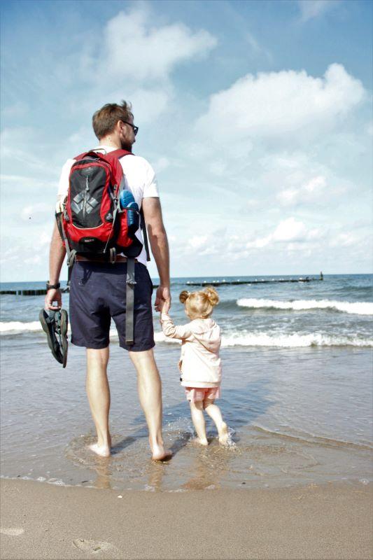 Tata z małą córeczką spacerują po plaży na bosaka.